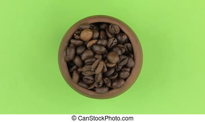 Zoom out, rotation of coffee beans in a clay pot, isolated...