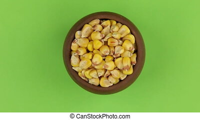 Zoom out, rotation of corn grains in a clay pot, isolated on...