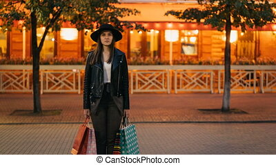 Zoom out time-lapse of serious young lady in fashionable garments standing outdoors in pedestrian street holding shopping bags and looking at camera, busy people are passing by.