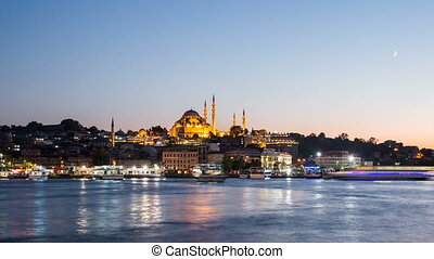 Zoom out Timelapse view of Istanbul cityscape with Suleymaniye mosque with tourist ships floating at Bosphorus at night