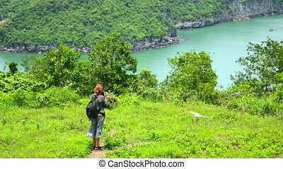 Zoom out - tourist girl taking picture, limestone halong bay
