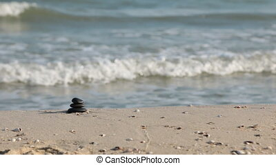 Zoom stones pyramid on sand, against the background of sea...