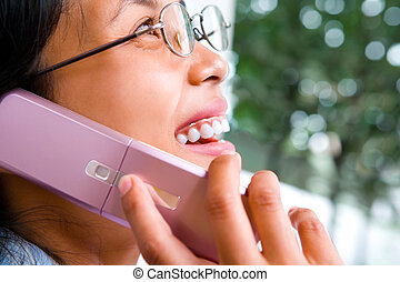 Zoomed face of a young woman using cell phone