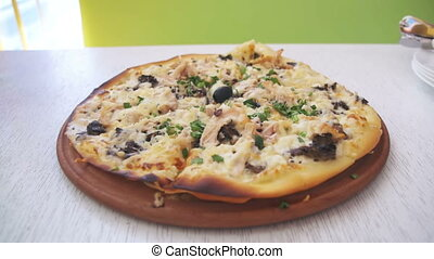 Zooming in to Pizza on a White Wooden Table in a Cafe
