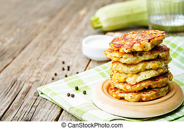zucchini corn fritters on a dark wood background. the toning...