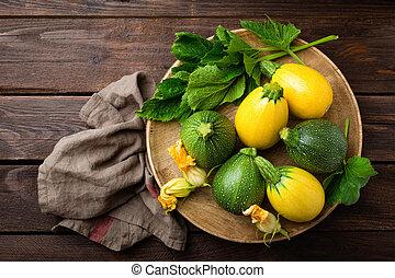 zucchini, met, bladeren, en, bloemen, op, donker, houten, rustiek, achtergrond