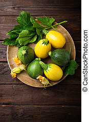 Zucchini with leaves and flowers on dark wooden rustic background