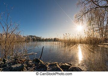 Zugefrorener See - Sonnenschein über dem gefrorenen...