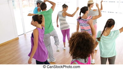 Zumba class dancing in studio at the gym