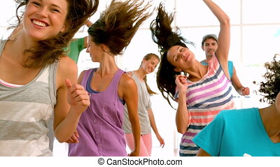 Zumba class dancing in studio in slow motion