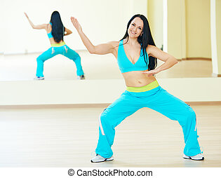 zumba firness instructor doing dancing exercises in sport club
