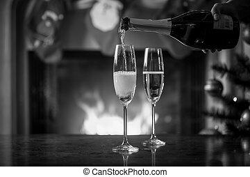 zwart wit foto, van, hand houdend, fles, en, vullen, bril, met, champagne, op, kerstmis, tafel