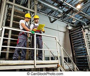 zwei, arbeiter, in, sicherheit, hüte, auf, a, fabrik, lesende , plan