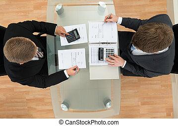 zwei, geschäftsmann, berechnend, rechnungen, gebrauchend, taschenrechner