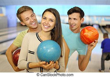 zwei, glücklich, maenner, und, m�dchen, halten, kugeln, in, sportkegeln, club;, fokus, auf, woman;, maenner, betrachten, woman;, zurück, von, junge, werfen, ball;, seicht, schärfentiefe