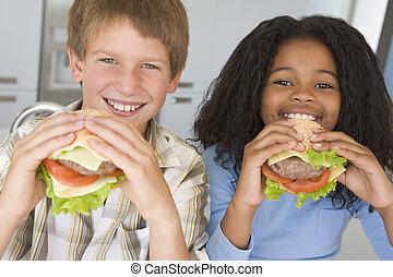 zwei, junge kinder, in, kueche , essende, cheeseburger, lächeln