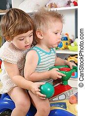 zwei kinder, in, spielzimmer, auf, spielzeug, motorroller
