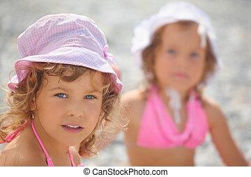 zwei, kleine m�dchen, auf, a, meer, coast., fokus, auf, m�dchen, tragen, rosa, panama, hat., noch ein, m�dchen, in, heraus, von, fokus.