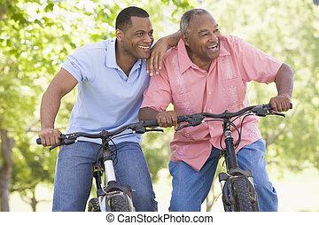 zwei männer, auf, fahrräder, draußen, lächeln