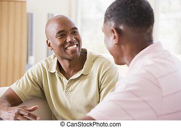 zwei männer, in, wohnzimmer, sprechende , und, lächeln