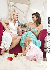zwei, mütter, in, wohnzimmer, mit, babys, und, bohnenkaffee, lächeln