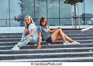 zwei, schöne , junger, freundinnen, sitzen, auf, skateboard, an, schritte, auf, a, hintergrund, von, der, skyscraper.